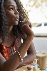 Portrait of young African woman eating a piece of cake and having a coffee - VEGF00702