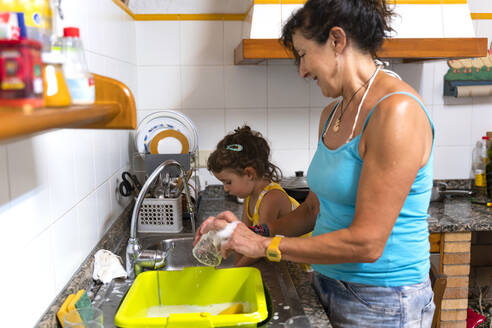 Little girl helping grandmother washing dishes in the kitchen at home - GEMF03136