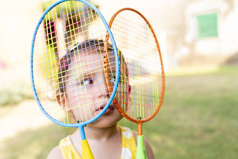 Little girl playing with colorful badminton rackets outdoors in summer - GEMF03145