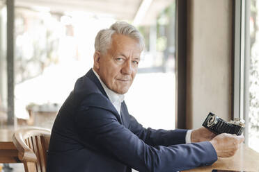 Portrait of senior businessman holding old-fashioned camera in a cafe - GUSF02632
