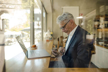 Senior businessman using cell phone in a cafe - GUSF02635