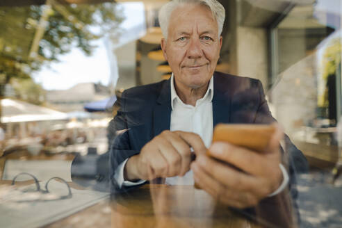 Portrait of senior businessman using cell phone in a cafe - GUSF02638