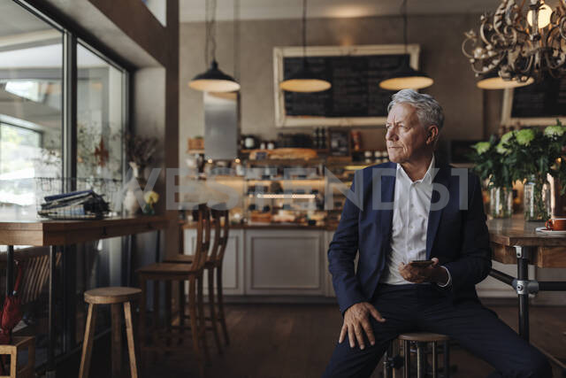Senior businessman with cell phone in a cafe - GUSF02644 - Gustafsson/Westend61