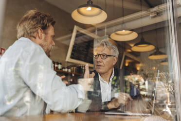 Two businessmen with laptop meeting in a cafe - GUSF02650