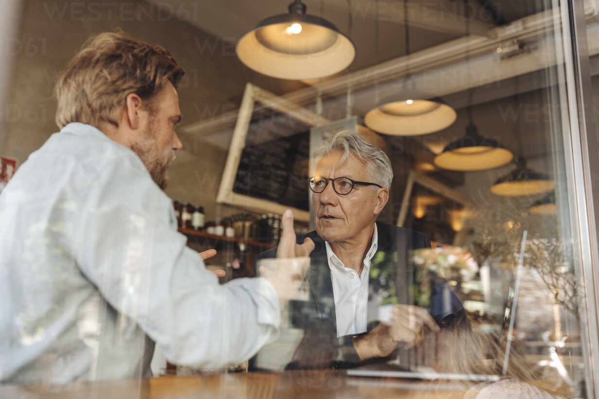 Two businessmen with laptop meeting in a cafe - GUSF02650 - Gustafsson/Westend61