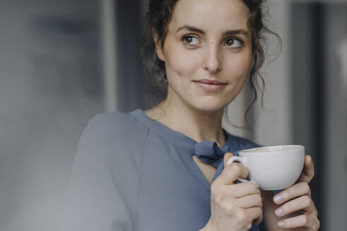 Portrait of young woman relaxing with cup of coffee - KNSF06554