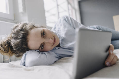 Portrait of smiling young woman relaxing at home using digital tablet - KNSF06569