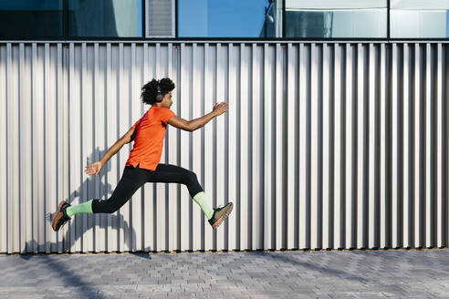 Young man jumping in the city, metallic wall in the background - JRFF03711