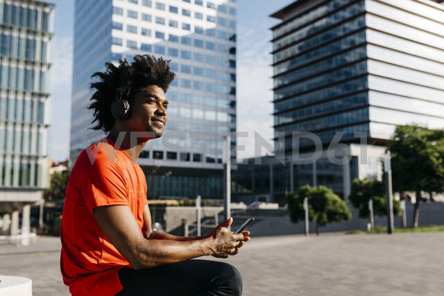 Young sportsman sitting on a bench, using smartphone and listening to music - JRFF03723 - Josep Rovirosa/Westend61