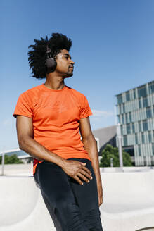 Young man jogging in the city, listening to music - JRFF03726