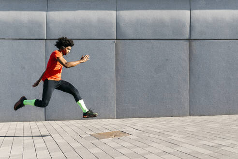 Young man jumping in front of a gray wall in the city, listening to music - JRFF03732