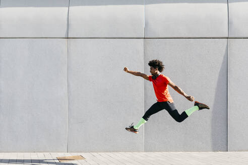 Young man doing jumps with a gray wall in the background - JRFF03741