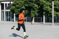 Young man jogging in the city, listening to music - JRFF03744
