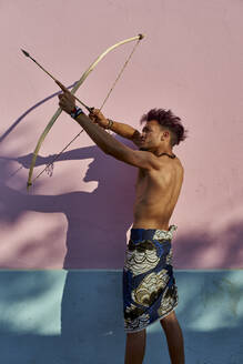 Barechested young man with bow and arrow outdoors - VEGF00709
