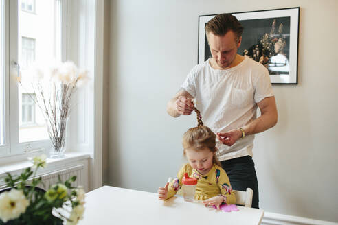 Father making daughters hair - JOHF00349