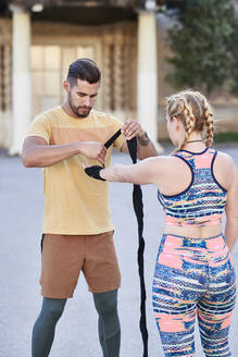 Fitness coach practicing boxing class with young woman outdoors in the city applying bandage - JNDF00093