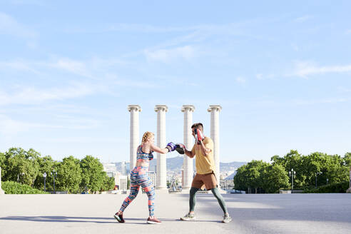 Fitness coach practicing boxing class with young woman outdoors in the city - JNDF00096