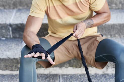 Close-up of boxer sitting on stairs applying bandage - JNDF00105