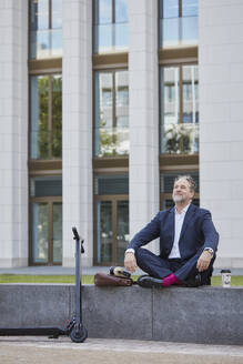Relaxed mature businessman sitting on wall in the city - RORF01846