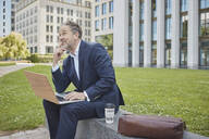 Mature businessman sitting on a wall in the city using laptop - RORF01852