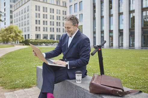 Happy mature businessman sitting on a wall in the city using laptop - RORF01855