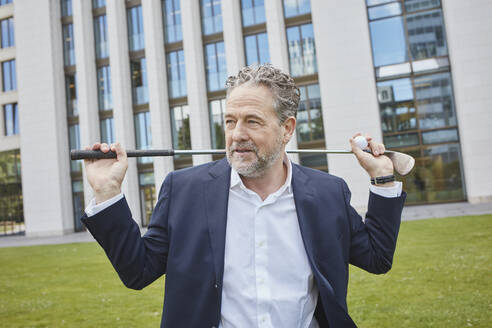 Mature businessman with golf club in the city - RORF01858