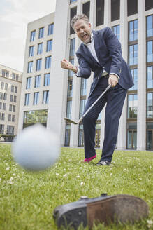 Happy mature businessman playing golf on lawn in the city - RORF01861