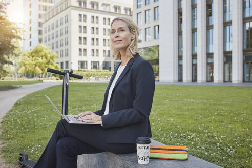 Businesswoman sitting on a wall in the city using laptop - RORF01876