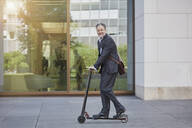 Businessman on e-scooter passing office building in the city - RORF01888
