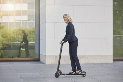 Businesswoman on e-scooter passing office building in the city - RORF01891