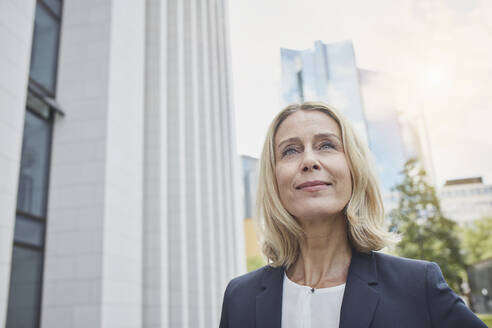 Portrait of confident blond businesswoman in the city looking up - RORF01894