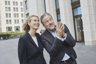Happy businessman and businesswoman in the city looking up - RORF01906