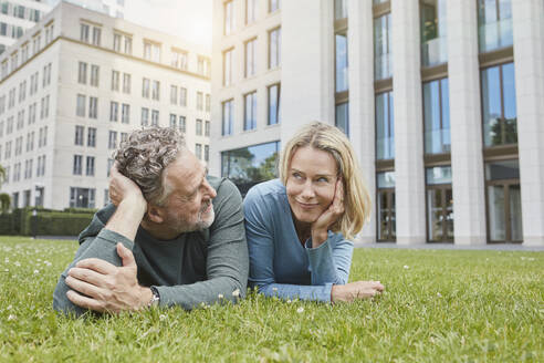 Relaxed mature couple lying on lawn in the city - RORF01924