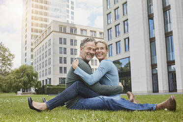 Happy mature couple sitting on lawn in the city - RORF01927