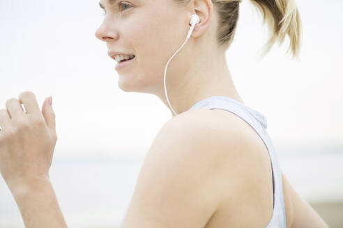 Young woman with earphones jogging - JESF00300