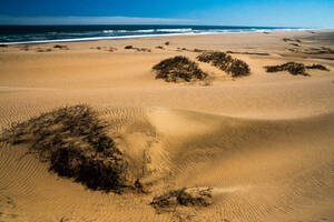 Sand dunes, blown by wind into pronounced furrows stretching into the distance by the sea and surf, near Sandwich Bay, Namibia, Africa - RHPLF10533