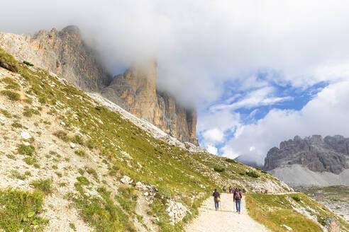 Tourists walks on the pathway for Three Peaks of Lavaredo, Dolomites of Sesto, Province of Belluno, Veneto, Italy, Europe - RHPLF10889