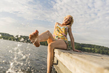 Young woman sitting on a jetty at a lake with feet in water - JOSF03598