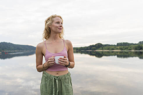 Young woman drinking coffee from cup at a lake - JOSF03601