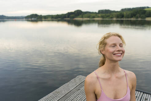 Smiling young woman with closed eyes on a jetty at a lake - JOSF03604