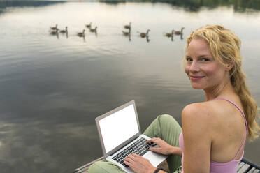 Young woman using laptop on a jetty at a lake - JOSF03610