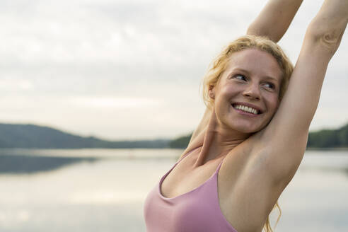 Happy young woman raising her arms at a lake - JOSF03619