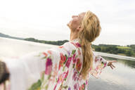 Happy young woman with outstretched arms at a lake - JOSF03622