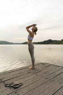 Young woman practicing yoga on a jetty at a lake - JOSF03628