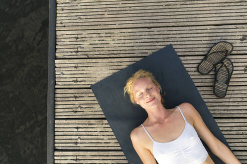 Top view of young woman lying on a jetty - JOSF03637