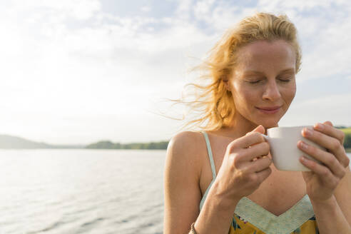 Young woman dwith closed eyes holding a cup at a lake - JOSF03640