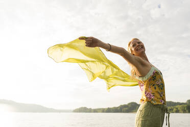 Happy young woman holding a cloth at a lake - JOSF03643