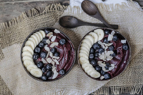 Directly above shot of ice cream served with banana slices and blueberries in bowls on table - STBF00376