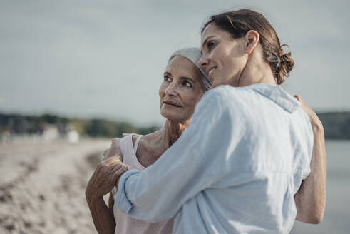 Mother and daughter spending a day at the sea, embracing on the beach - JOSF03647