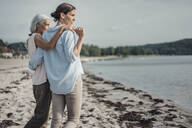 Mother and daughter spending a day at the sea, embracing on the beach - JOSF03650